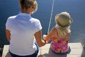 Woman and young girl fishing from pier