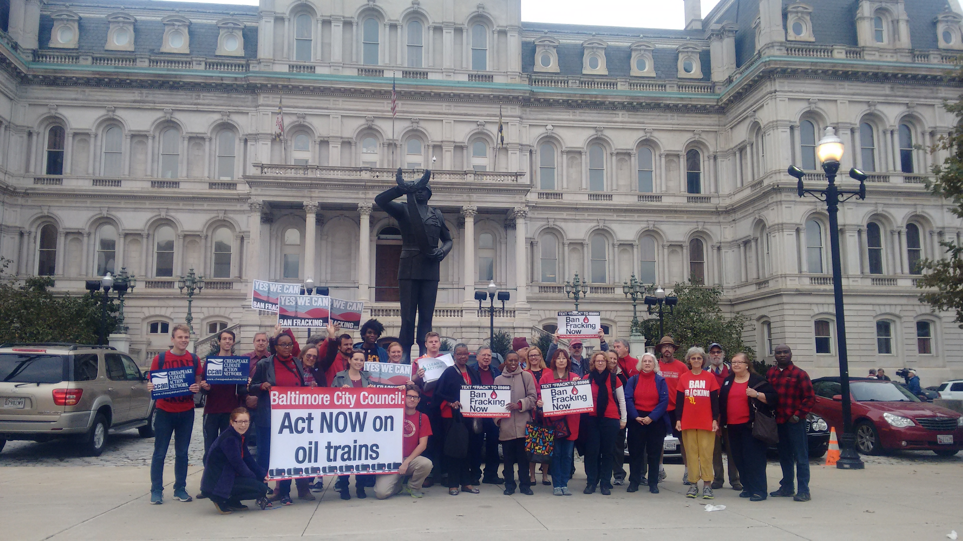 Over 30 Baltimore residents outside of City Hall wearing red in support of the Oil Trains Ordinance and the Fracking Ban