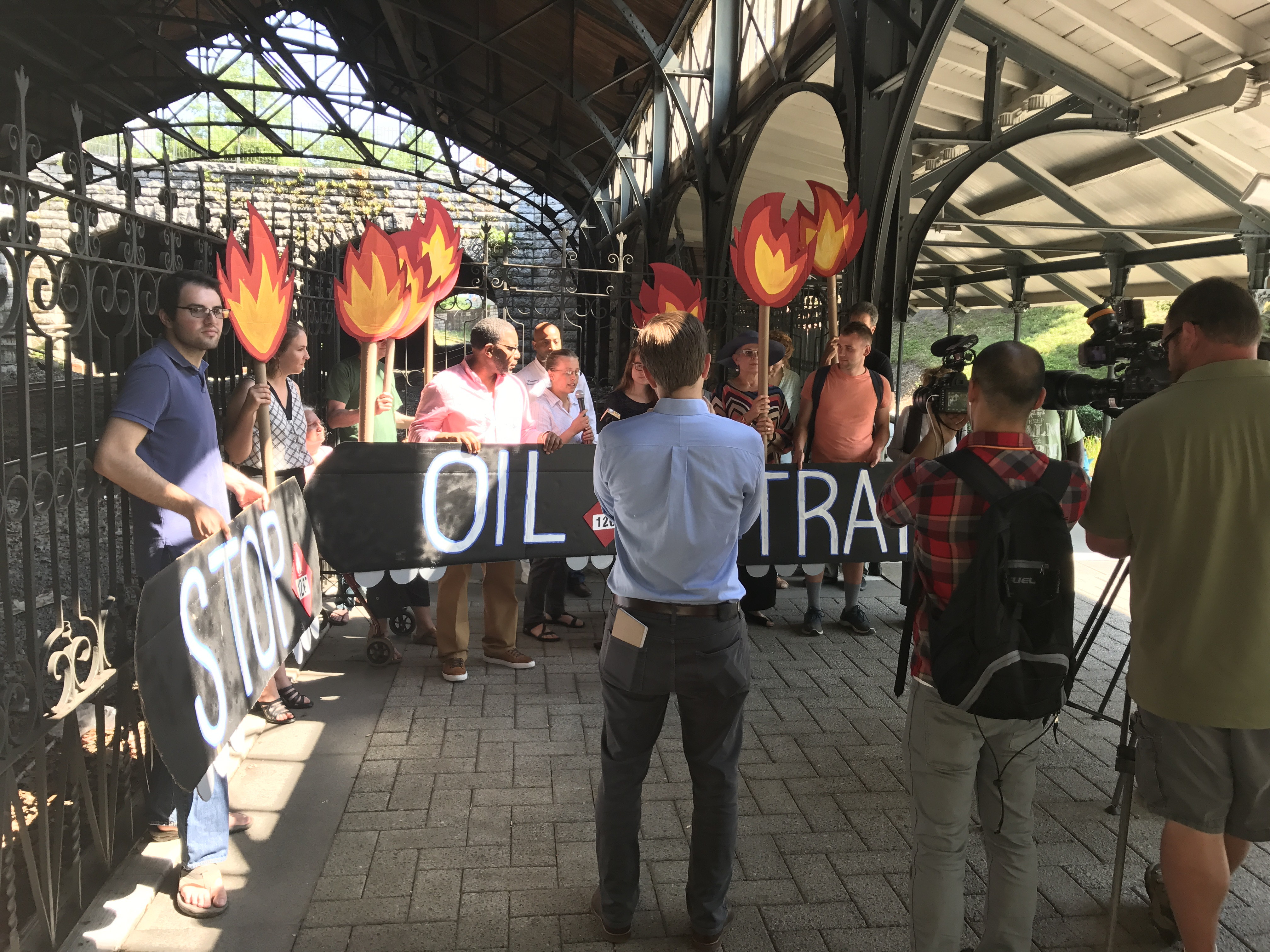 "15 people hold signs saying ""Stop Oil Trains"" and showing train tank cars and flames as news media films"