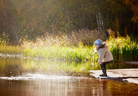 A young girl playing on the edge of a lake. Photo credit: Sk Elena / Shutterstock